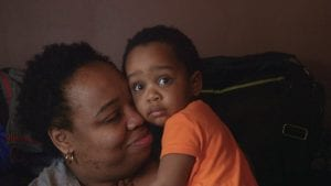 Still photo from The Place that Makes Us, a documentary about Youngstown, Ohio. Image shows a woman holding a small child.