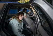 A girl leans against the seat of a car, seemingly tired.