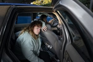 A girl leans against the seat of a car, seemingly tired. Family homelessness