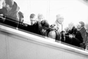 a black and white photo of people on a stairwell, so people are blurry. This image represents cities have led the way in enacting equity-focused pandemic policies.