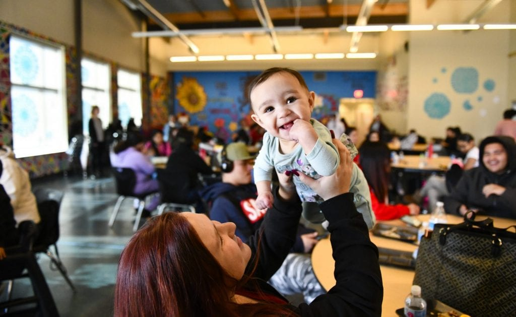 Photo shows a smiling baby being held up by a woman, at a Denver charter school developed by the Urban Land Conservancy, which operates like a commercial CLT.