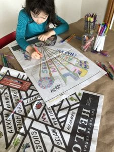 A young child uses crayons to color in an image on paper. Photo courtesy of Seattle Housing Authority.
