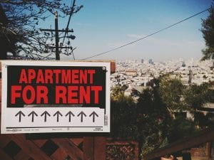 """To illustrate article about rent forgiveness, photo shows """"apartment for rent"""" sign with a row of up arrows."""