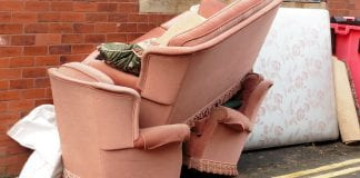 A sofa and two matching chairs in pink upholstery are piled up on the sidewalk, next to a mattress.