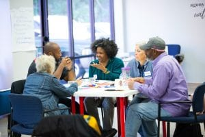 A group of people of varying ages sit together at a table having a discussion, to illustrate an article about healthy design for affordable housing