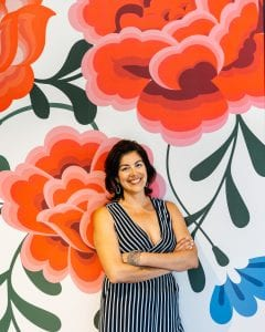 Photo of Irma Robinson, co-owner of a catering business helped by Pacific Community Ventures, standing before a large floral backdrop. PCV focuses its work on good job creation.