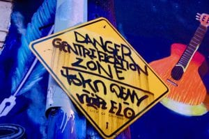 """Close-up of a yellow sign hand painted with the words """"Danger/Gentrification/Zone"""""""