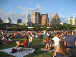 A crowd of people relaxing in an Austin, Texas, park in the evening, with the city skyline visible in the background, accompanying an article on cities with a high rate of population growth.