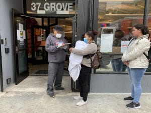A man with a clipboard speaks to a woman holding a baby, while another woman waits in line behind her. Accompanying an article about the coordinated entry approach to housing the homeless.