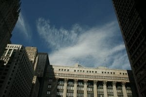 A view looking up toward the top of Chicago City Hall, with blue sky above it. Accompanying an article about the city's REIA and resulting new QAP.