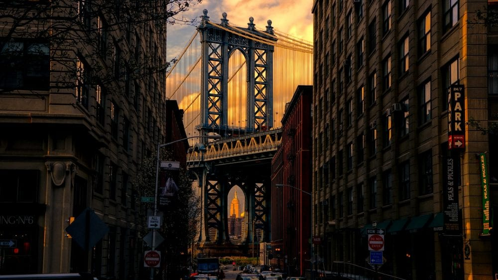 The Brooklyn Bridge framed by large buildings. Interboro Community Land Trust currently has several projects occurring in Brooklyn and Queens New York.