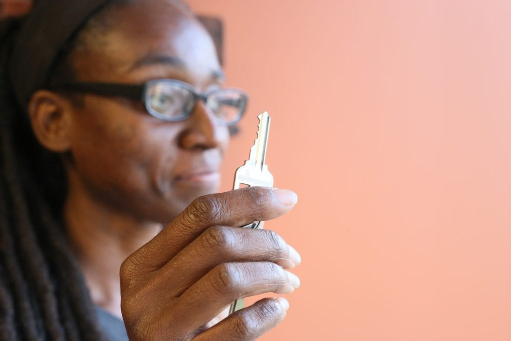 Photo of Makeisha Robey holding a key (in the foreground, in focus) to her new home, purchased through the Atlanta Land Trust.