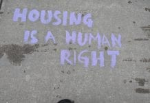 """In purple chalk, it says """"Housing is a Human Right."""""""