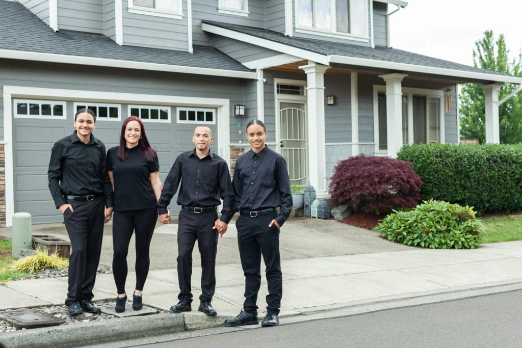 Four young, smiling people stand holding hands in front of a gray house, purchased through the Proud Ground CLT.