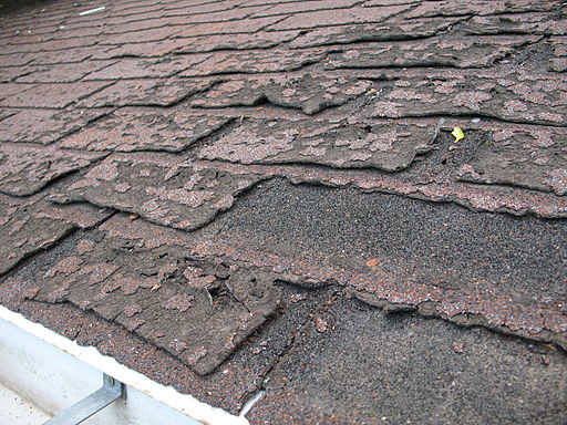 Close-up view of dilapidated asphalt roof shingles, illustrating article about the Biden infrastructure plan and its potential for affordable housing
