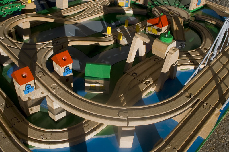 A view from above of wooden toy train tracks with trestles, ramps, houses, and bridges, illustrating article on Biden's infrastructure plan