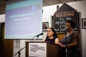 """Two women stand at a lectern presenting findings. Near them is a screen onto which is projected the words """"Health Neighborhoods Research Study"""""""
