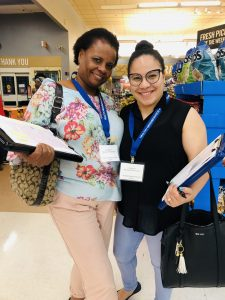 Two women stand together in a supermarket, both holding clipboards and wearing nametag lanyards, both participating in the Healthy Neighborhoods Study in Lynn, Mass.dy