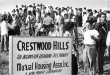 """A black-and-white photo showing a large group of milling people near a sign that reads """"Crestwood Hills/For information regarding this property/Mutual Housing Assn. Inc."""""""