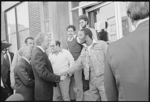 A black-and-white photo from October 1977 showing President Jimmy Carter shaking the hand of a Black man on the steps of a building in the South Bronx. Several other people stand nearby, including New York Mayor Abe Beame.