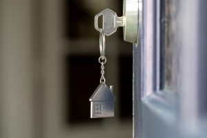 Open door to a new home with key and home shaped keychain.
