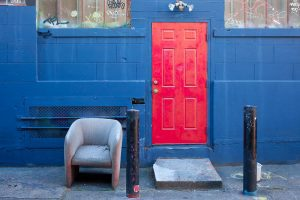 A bright red door contrasts strongly with the blue of the wall, in a cropped photo of a building. Illustrating an article about Democratic housing policies