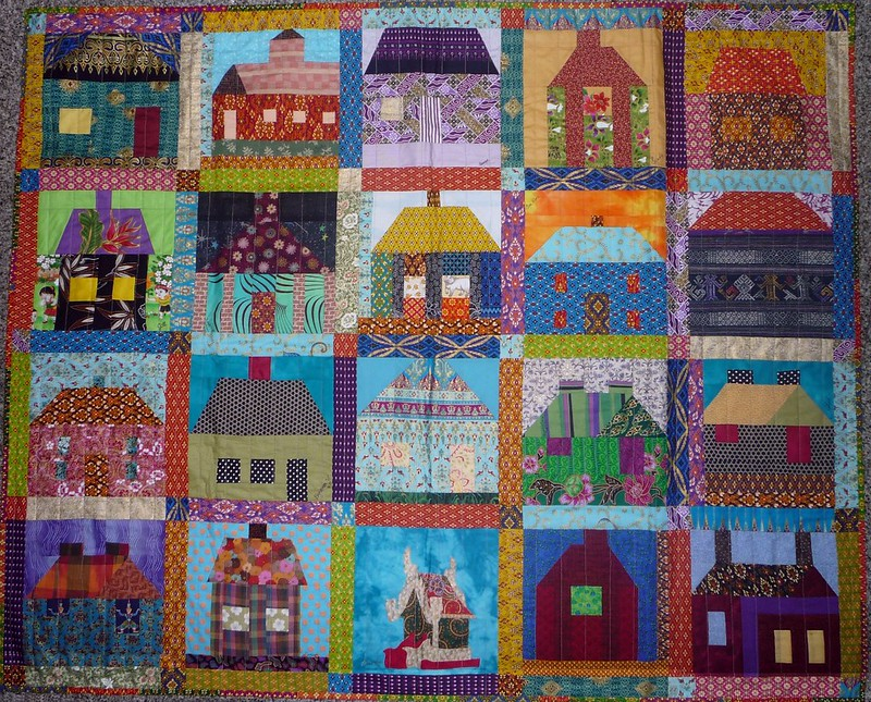 View of a quilt with 20 blocks, each with a house, all in different styles and colors, to illustrate the patchwork nature of housing assistance in the U.S.