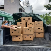 Housing organizations pivot from their traditional services to offering COVID testing and vaccinations. Photo is a view of a pickup truck, the bed stacked high with cartons full of food. A woman at left, wearing a mask, loads cartons onto the truck.