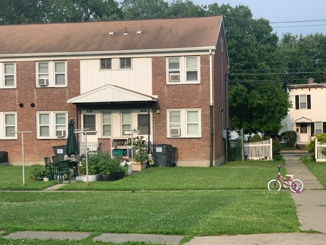 A view of one of the Saratoga Sites units, a brick two-story building, with potted plants and outdoor furniture in front, and a child's bike on the sidewalk.