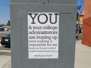 """A poster on a utility box reads: """"You & our college administrators are buying up land making it impossible for my family and friends to afford neighborhood we grew up in. Illustrating an opinion piece recommending studying gentrification"""