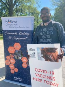 A smiling man stands near a banner for the Famicos Foundation in Cleveland and holds up a poster announcing that COVID-19 vaccines are being offered.