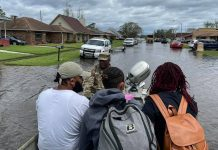 A National Guardsmen rescues three people on a boat in LaPlace, Louisiana,after Hurricane Ida brought flooding to the area.